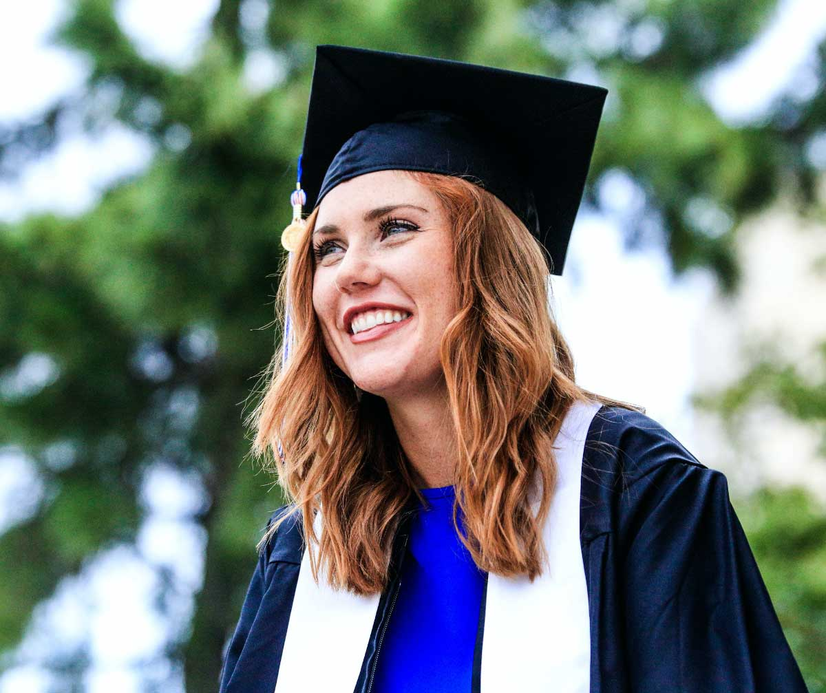 A young woman with auburn hair in graduation attire
